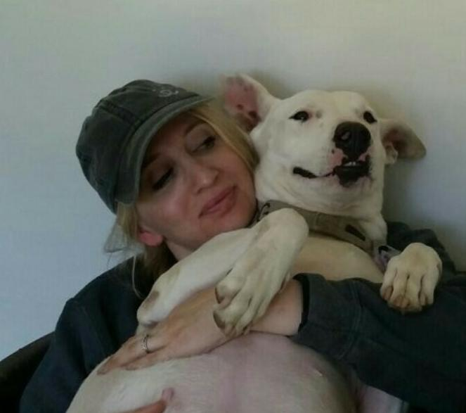 Volunteer Sam snuggling with a white dog