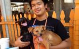 Volunteer Austin Delos Santos holding two small dogs